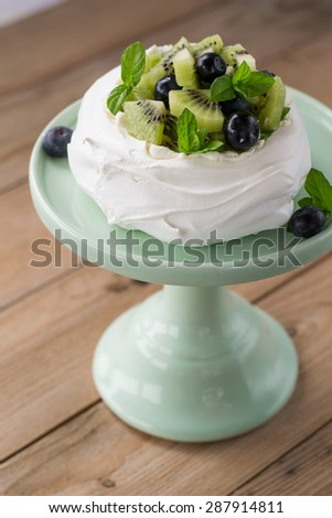 Pavlova with kiwi and blueberries decorated with mint leaves. Served on the mint cake stand. - stock photo