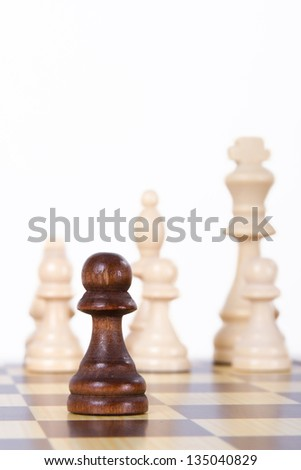 Pawn against opponent chess pieces on board, isolated on white background. - stock photo