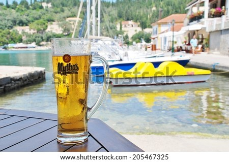PAXOS, GREECE - JUNE 16, 2014: A cold glass of Mythos beer in front of the harbour at Lakka on the Greek island of Paxos. Made by the Mythos Brewery company, the popular brand was launched in 1997. - stock photo