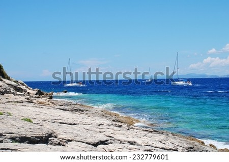 PAXOS, GREECE - JUNE 19, 2014: Sailing boats pass the rocky Arkoudaki beach at Lakka on the Greek island of Paxos. Lakka is the Northern port of the 13km long Ionian island. - stock photo