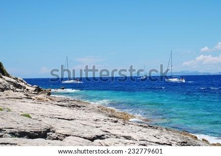 PAXOS, GREECE - JUNE 19, 2014: Sailing boats pass the rocky Arkoudaki beach at Lakka on the Greek island of Paxos. Lakka is the Northern port of the 13km long Ionian island. - stock photo