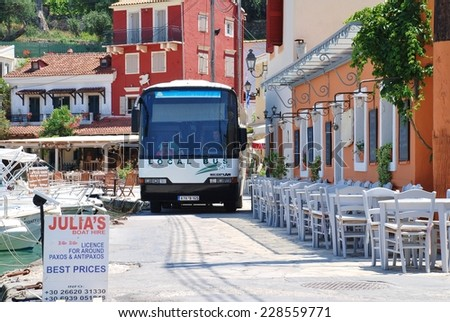PAXOS, GREECE - JUNE 14, 2014: The local island bus negotiates the narrow seafront road at Loggos on the Greek island of Paxos. Taverna diners have to vacate their chairs to let the bus pass. - stock photo