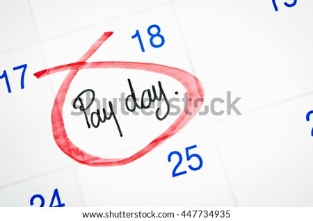 Pay day written with red mark on a calendar page. - stock photo