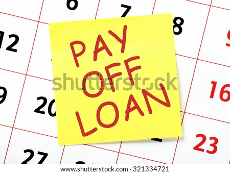 Pay Off Loan message in red text on a yellow sticky note posted on a wall calendar as a reminder - stock photo