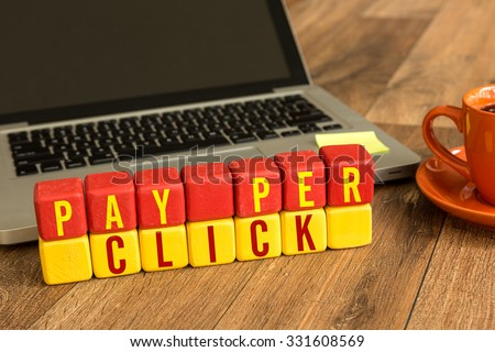 Pay Per Click written on a wooden cube in front of a laptop - stock photo