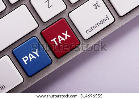 Pay tax button on white computer keyboard