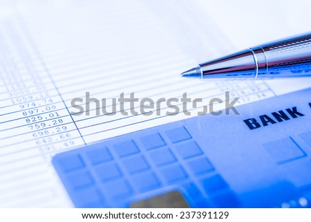 Pay the bills, bank card and pen on the table. In blue tone