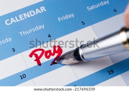 Pay word written on the calendar with a pen - stock photo