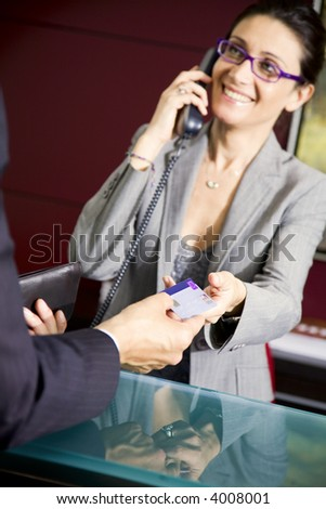Paying by credit card: young salesclerk smiling at a customer - stock photo