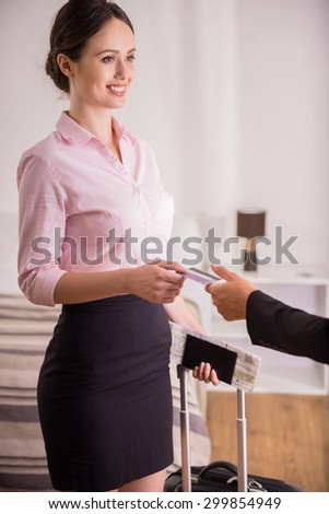 Paying for the hotel room. Businesswoman standing on the hotel room with suitcase and documents and giving a credit card to doorman. - stock photo