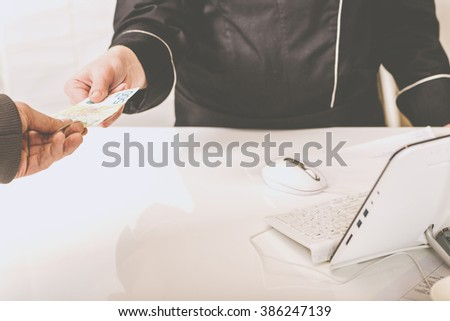 Paying with Cash at Clothing Shop Counter. Customer Paying with Cash in the Apparel Shop. Woman Paying for Goods in Nursery Shop of a Shopping Center. Man Paying for Groceries at Supermarket Checkout - stock photo