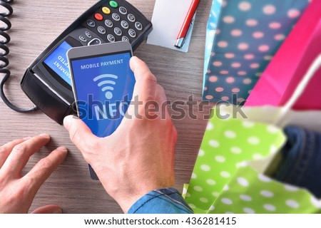 Payment in a trade with nfc system with mobile phone. Top view,vertical composition - stock photo