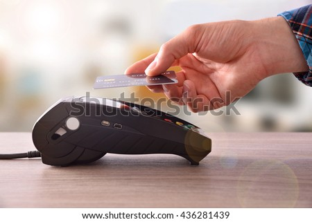 Payment on a trade through contactless card and NFC technology. Front view. Horizontal composition. - stock photo