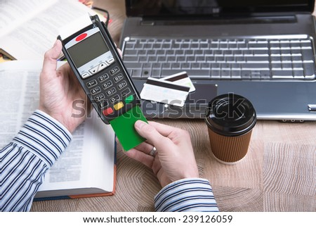 Payment terminal in the office. Laptop in the background - stock photo