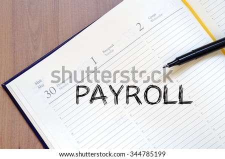 Payroll text concept write on notebook with pen