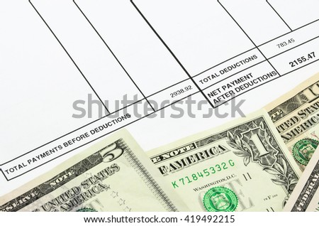 Payslip shows amount of earn with banknotes and coins - stock photo