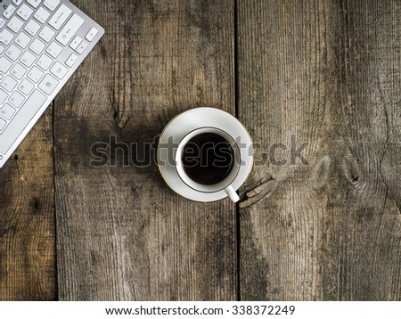 PC keyboard and cup of coffee on old weathering wooden table - stock photo