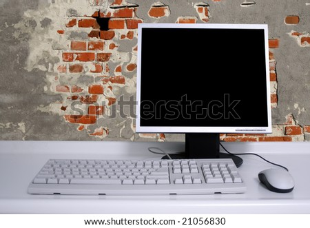 PC with black desktop  and old grunge brick wall background - stock photo