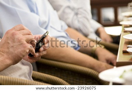 PDA in hands of a businessman at the restaurant table - stock photo