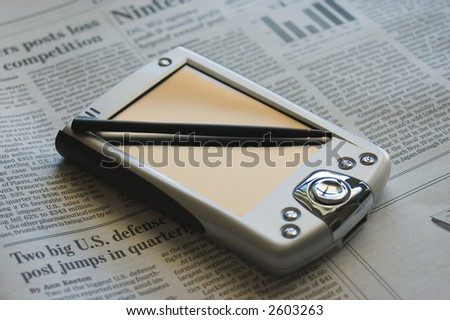 PDA over a newspaper - stock photo