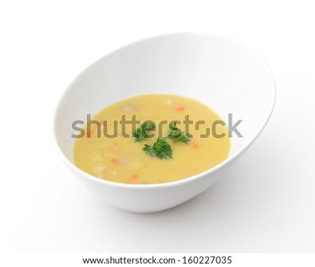 Pea Soup - A bowl of yellow split-pea soup on a white background. - stock photo