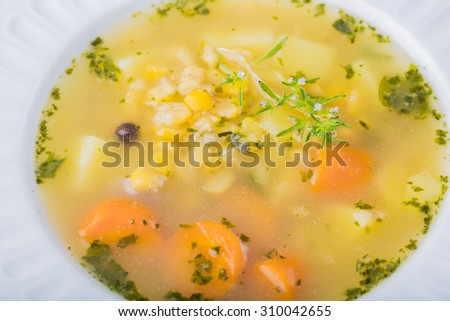 Pea soup in white plate on wooden table