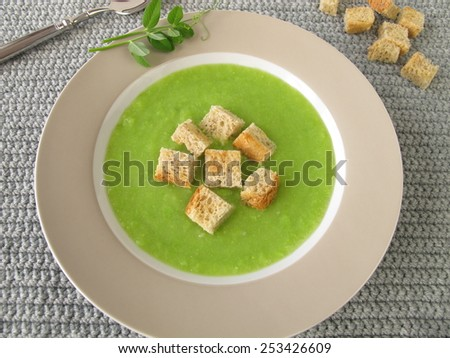 Pea soup with croutons - stock photo