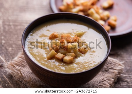 Pea soup with croutons in bowl on wooden background in rustic style. Selective focus.