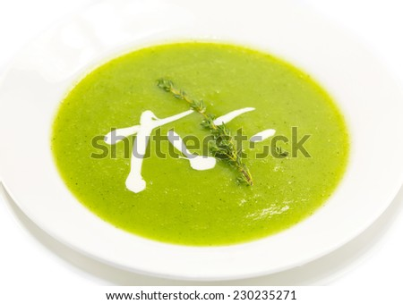 pea soup with croutons on a white dish at restaurant - stock photo
