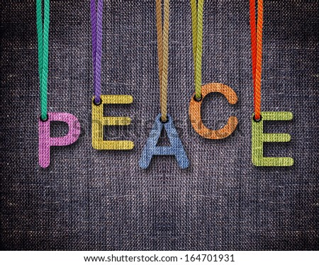 Peace Letters hanging strings with blue sackcloth background. - stock photo