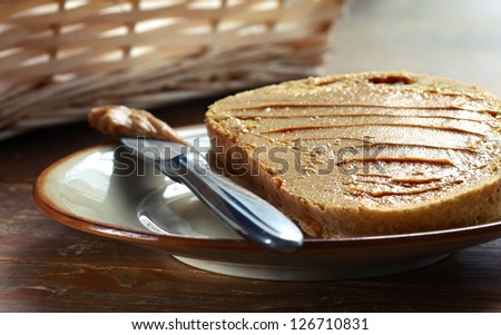 Peace of white bread spread with peanut butter with knife on the plate - stock photo