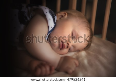 Peaceful adorable baby sleeping on his bed in a room at night. Soft focus. Sleeping baby concept. 1 year-old babyboy sleeps at home, dark background with light from the lamp