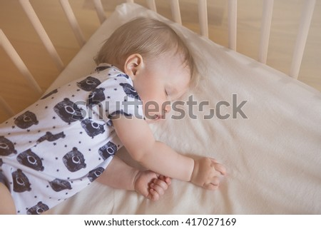 Peaceful adorable baby sleeping on his bed in a room. Soft focus. Sleeping baby concept. year-old babyboy sleeps at home - stock photo