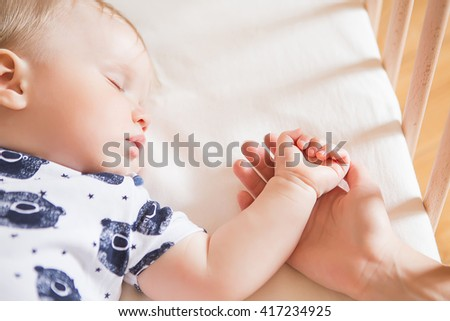Peaceful adorable baby sleeping on his bed in a room. Soft focus. Sleeping baby concept. year-old babyboy sleeps at home close up. Mum holds by the hand her sleeping child - stock photo