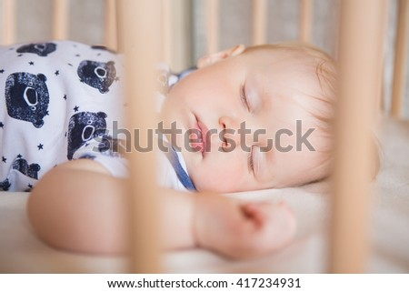 Peaceful adorable baby sleeping on his bed in a room. Soft focus. Sleeping baby concept. year-old babyboy sleeps at home close up - stock photo