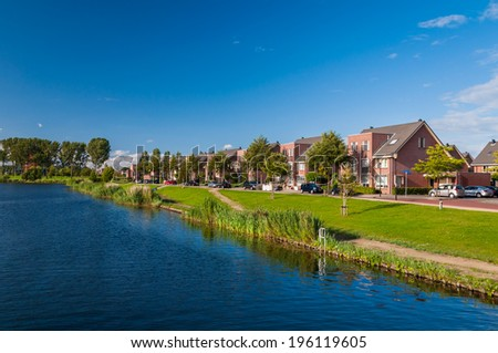 Peaceful and quiet suburban area with modern expensive houses on lake in Europe - stock photo