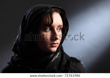 Peaceful and serene lighting of beautiful young woman wearing black hijab, looking away over her shoulder. - stock photo