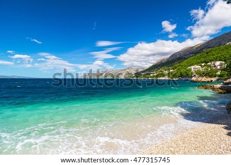 Peaceful and transparent summer blue sea, mountainous landscape in the background