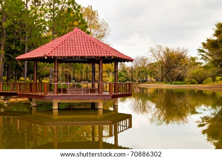 Peaceful asian garden with a wooden pavilion on a beautiful lake - stock photo
