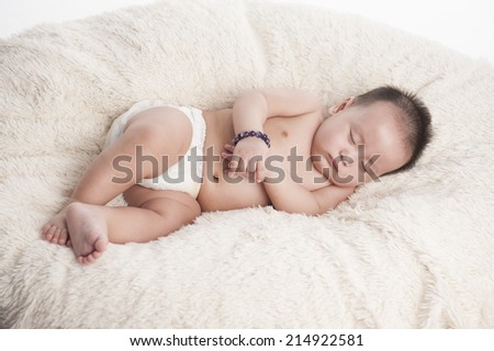 Peaceful baby lying on a bed - stock photo