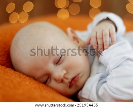 Peaceful baby lying on a bed while sleeping - stock photo