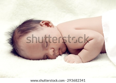 Peaceful baby lying on a bed while sleeping in a bright room over white sheet