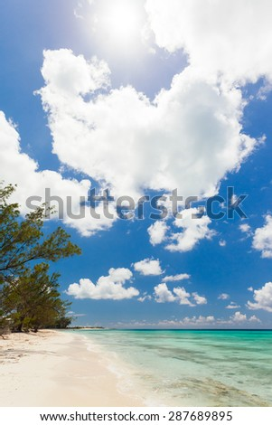 Peaceful beach with crystal clear water and cloudy sky in the Bahamas - stock photo