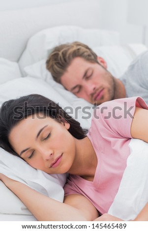 Peaceful beautiful couple sleeping in bed - stock photo