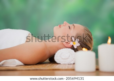 Peaceful blonde lying on bamboo mat with candles at the health spa