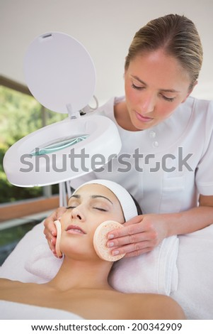 Peaceful brunette getting facial from beauty therapist in the health spa