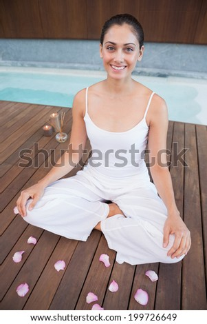 Peaceful brunette in white sitting in lotus pose surrounded by petals in health spa - stock photo