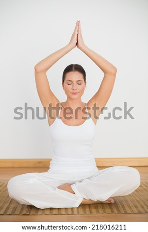 Peaceful brunette sitting and meditating in lotus pose in a white room - stock photo