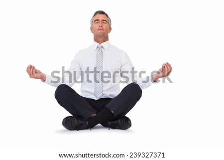 Peaceful businessman sitting in lotus pose on white background