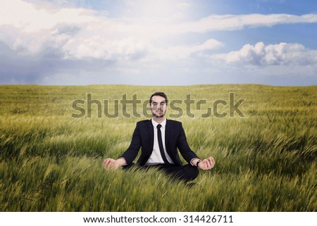 Peaceful businessman sitting in lotus pose relaxing against nature scene